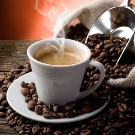 Rioba cafea boabe pentru rasnita de cafea langa ceasca de espresso fierbinte