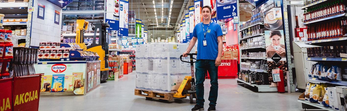 radnik u distributivnom centru prenosi paletu robe